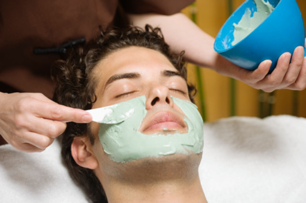 Man receiving green mud mask from beautician